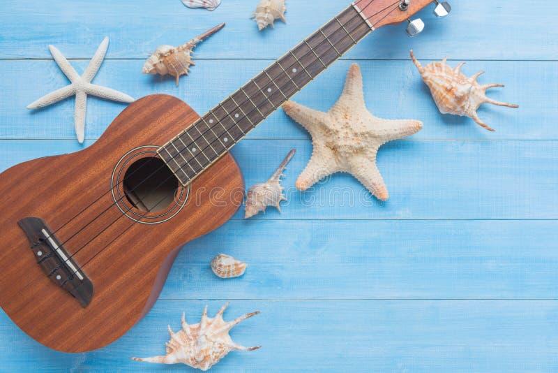 在浅兰的木板条地板上的尤克里里琴和海壳为夏天 免版税图库摄影