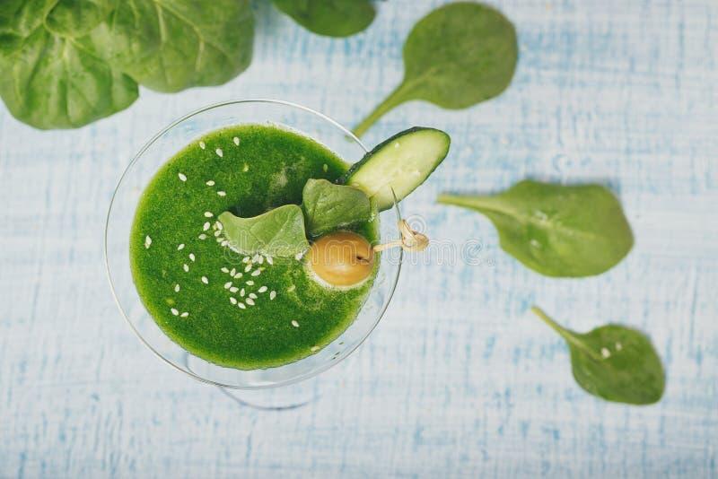 在浅兰的木backgro的绿色菠菜和黄瓜圆滑的人 免版税库存照片