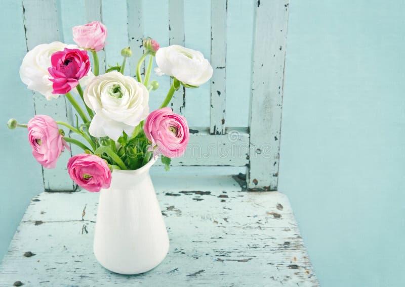 在浅兰的椅子的空白和桃红色花 免版税库存图片