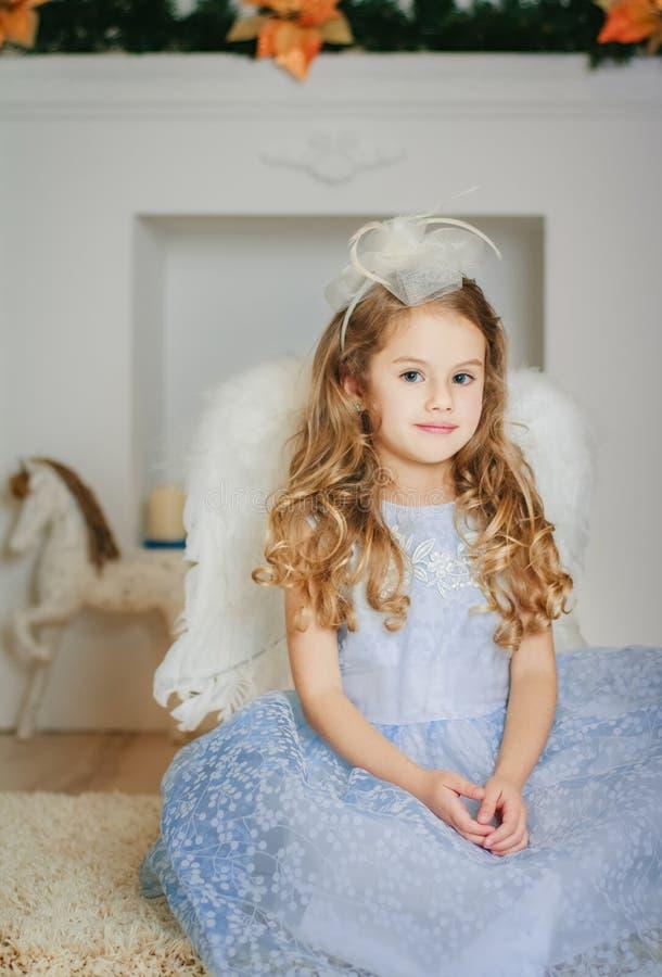 在浅兰的礼服等待的圣诞节的一点天使 免版税库存图片