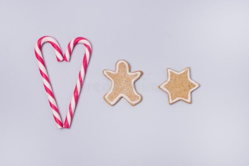 在浅兰的背景平的被放置的假日概念曲奇饼棒棒糖的圣诞节自创姜饼曲奇饼在心脏Chr形状  库存照片