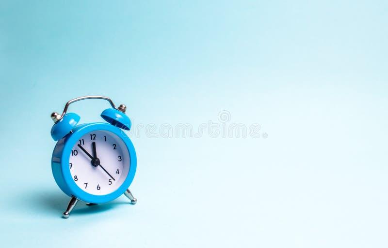 在浅兰的背景的一个蓝色闹钟 等待会议的概念,日期 守时 每小时工作的费用 库存图片