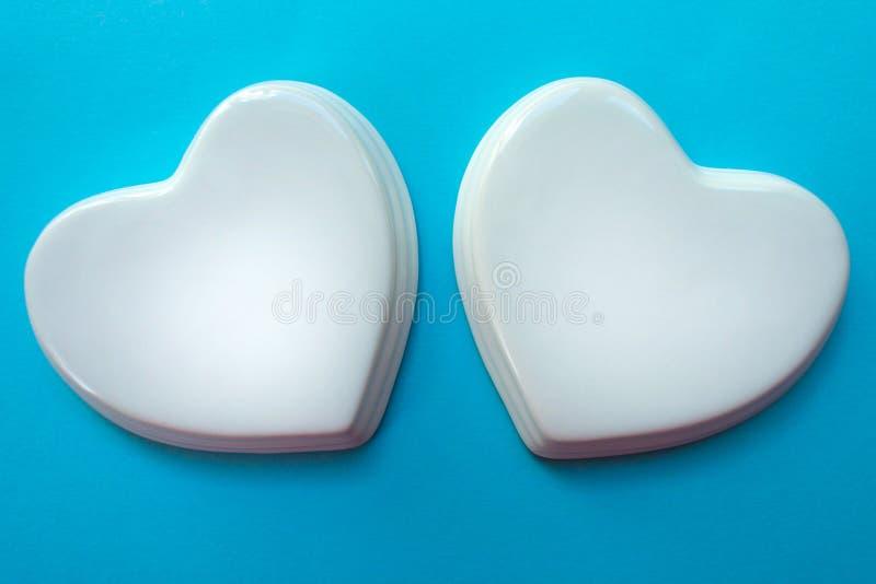 在浅兰的背景的两白色光滑的瓷心脏;喜帖;爱笔记 库存图片