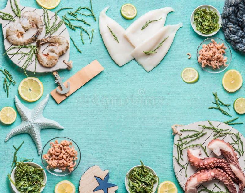 在浅兰的背景的各种各样的海鲜用乌贼、大虾或老虎虾、章鱼、北海螃蟹和海草,顶视图 免版税库存照片