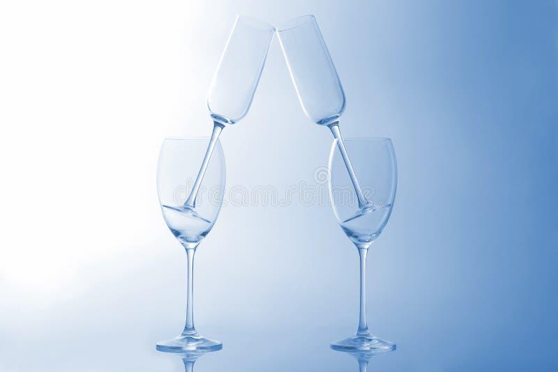 在浅兰的背景的四个空的酒杯 库存照片