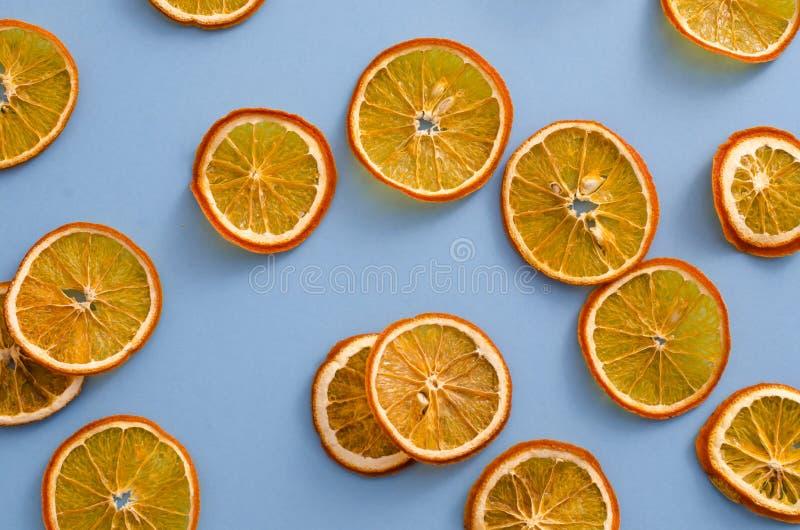 在浅兰的背景的干切片桔子柑桔 自创自然芳香装饰 假日的概念 与圣诞节结婚 库存图片