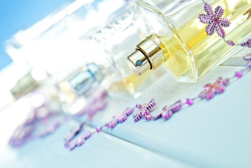 在浅兰的背景的透明香水瓶 秀丽产业 在明亮的颜色的图片 免版税库存图片