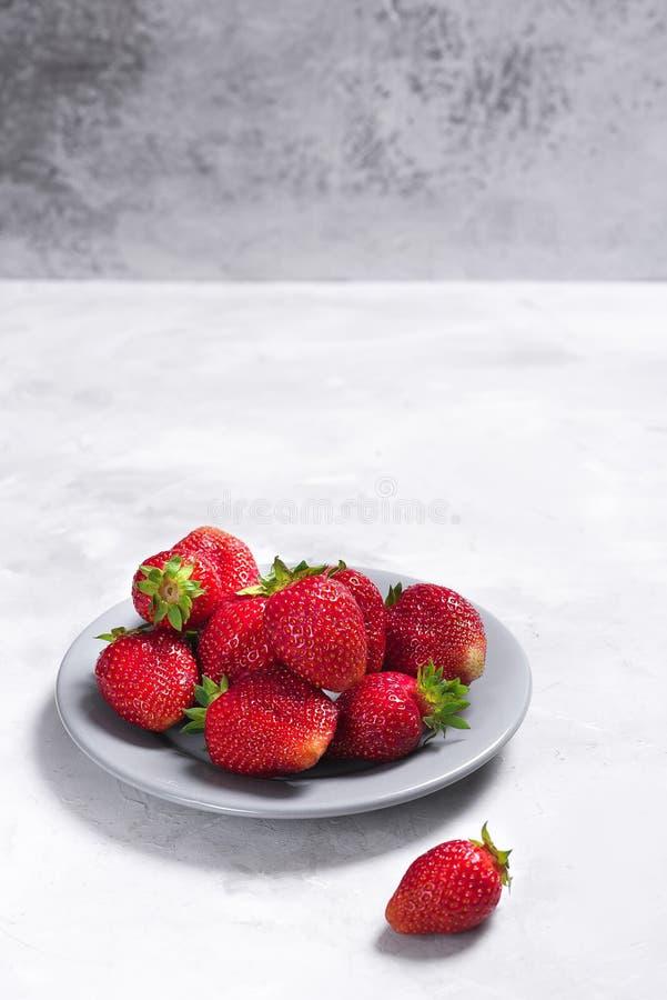 在浅灰色的背景的大水多的草莓 免版税库存图片