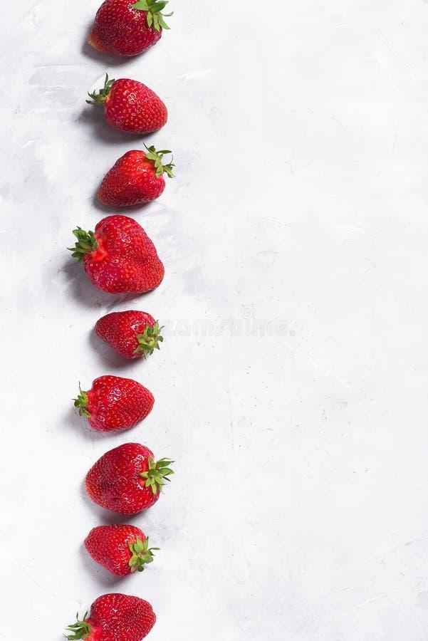 在浅灰色的背景的大水多的草莓 库存照片