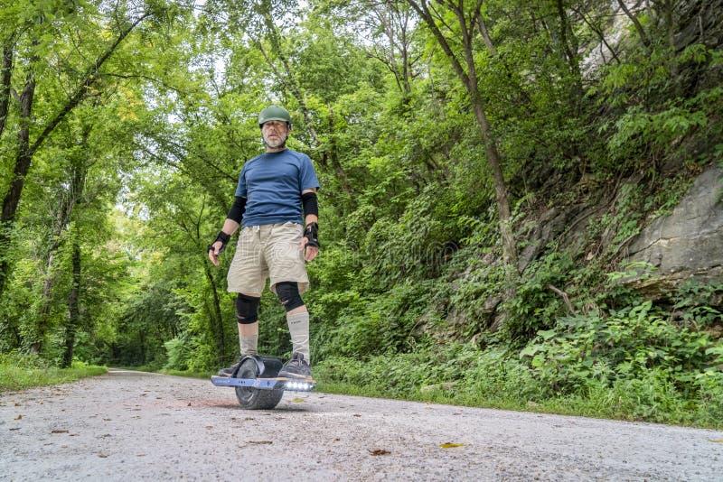 在浅田足迹的骑马onewheel电滑板 图库摄影
