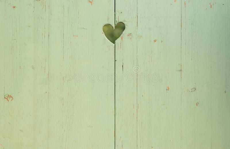 在浅绿色的木板条背景中雕刻的土气爱心脏 免版税库存图片