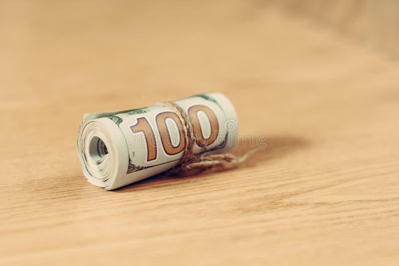 在浅褐色的背景的一百元钞票的卷 免版税图库摄影