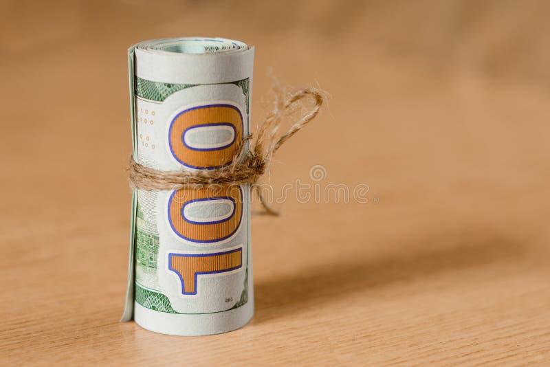 在浅褐色的背景的一百元钞票的卷 库存照片
