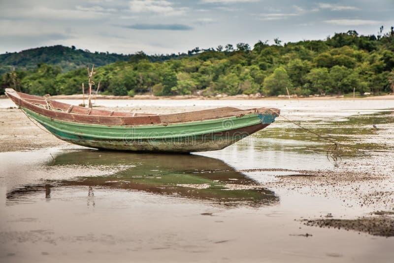 在浅滩的传统亚洲小船在热带海滩的低潮期间在阴暗天 免版税库存照片