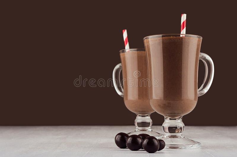 在浓咖啡玻璃的豪华甜巧克力点心用圆的巧克力和红色镶边秸杆在黑褐色背景 库存照片