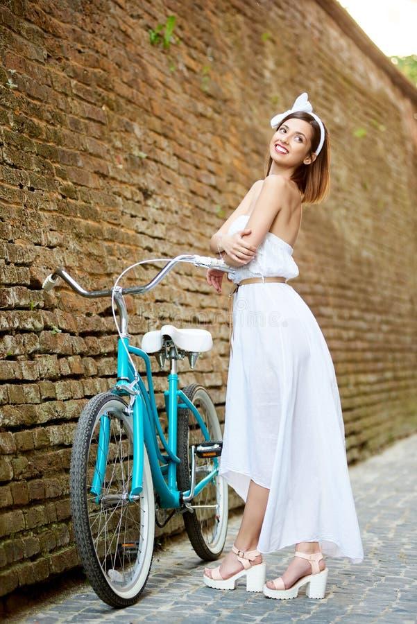 在浪漫图象的模型在葡萄酒自行车,砖墙附近摆在 免版税图库摄影
