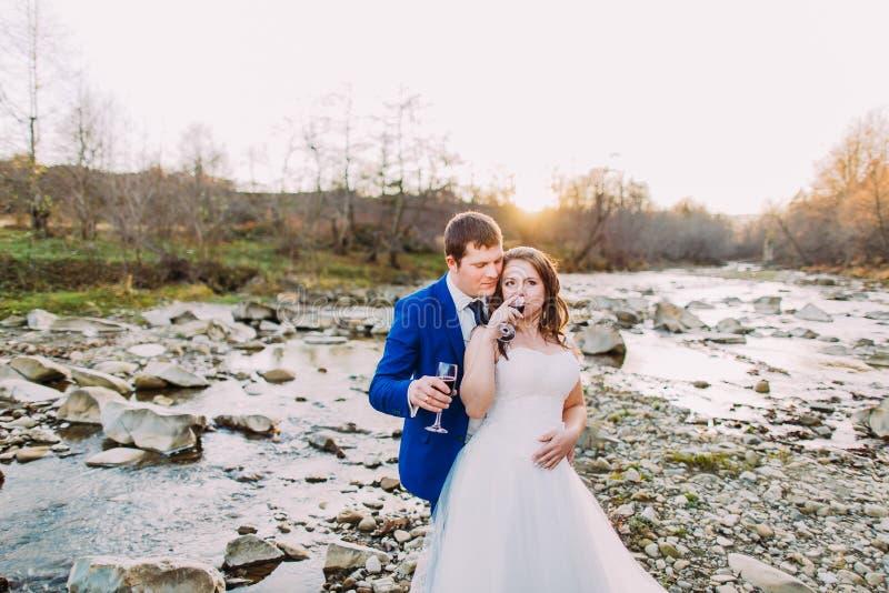 在浪漫岩石小卵石河岸的新婚佳偶对饮用的酒有Forest Hills和小河的 免版税库存照片