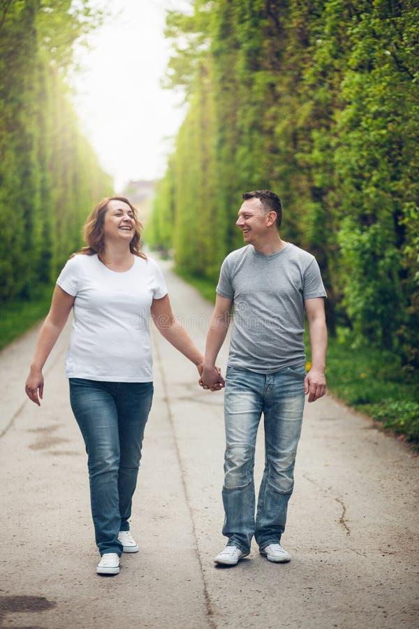 在浪漫步行的愉快的爱恋的夫妇户外在公园 免版税库存图片