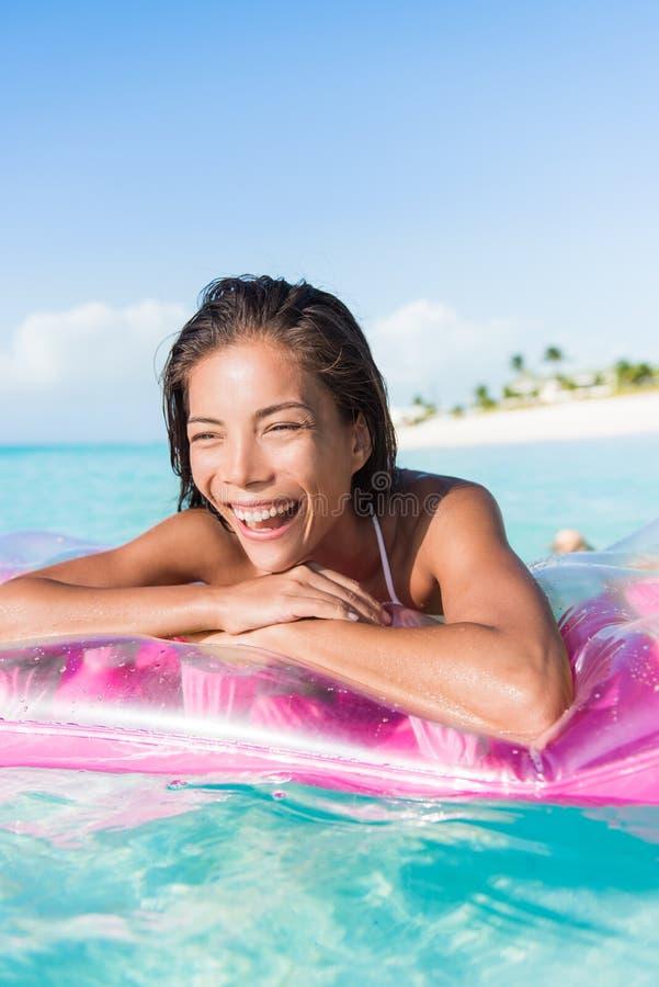 在浮游物床上的愉快的海滩妇女海洋游泳 图库摄影