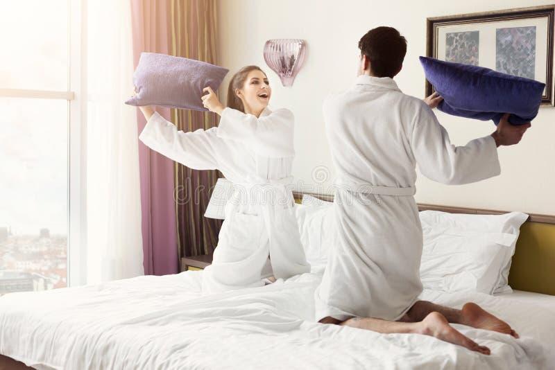 在浴巾的年轻愉快的夫妇与在床上的枕头战斗 库存照片