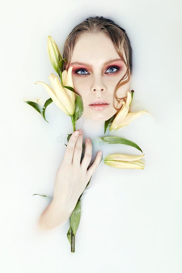 在浴的女孩用牛奶和百合在他的手上 妇女画象浪端的白色泡沫和花的在手中 皮肤回复,身体 免版税库存照片