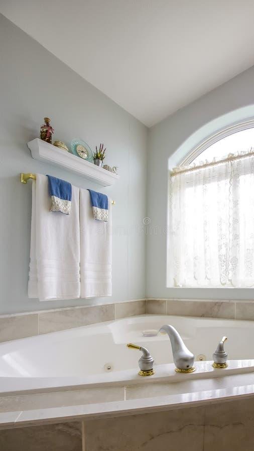 在浴缸修造的垂直高在一个卫生间的角落有一个大被成拱形的窗口的 免版税库存图片