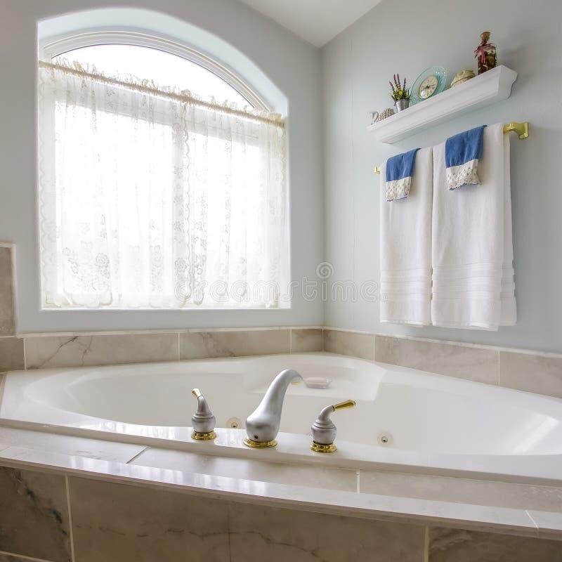 在浴缸建立的方形的框架在一个卫生间的角落有一个大被成拱形的窗口的 免版税库存图片