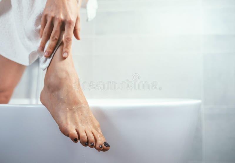 在浴缸的穿着考究的妇女` s脚渐近 免版税库存照片