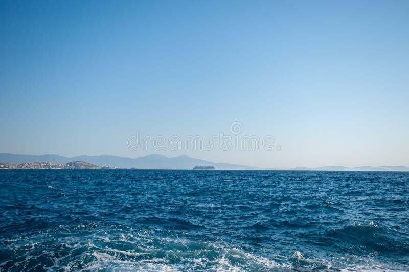 在海、天空蔚蓝和山的高速游艇在背景 在昂贵的豪华游艇滑翔的令人惊讶的看法海表面上 ?? 免版税库存图片