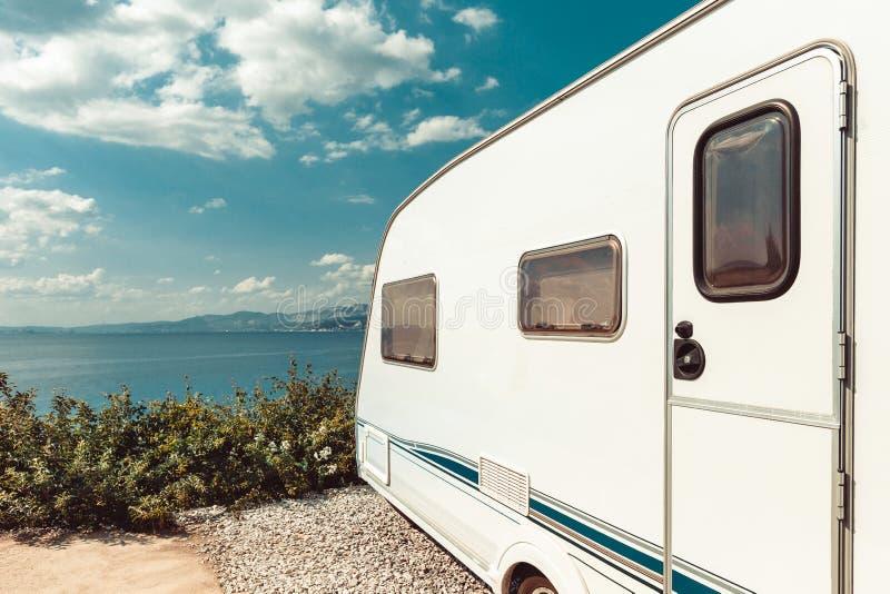 在海、海滩和蓝天附近的有蓬卡车拖车 暑假Ro 免版税图库摄影