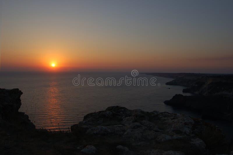 在海上的日落,山 免版税库存照片