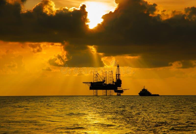 在海中间的近海杰克船具日落时间的 库存照片