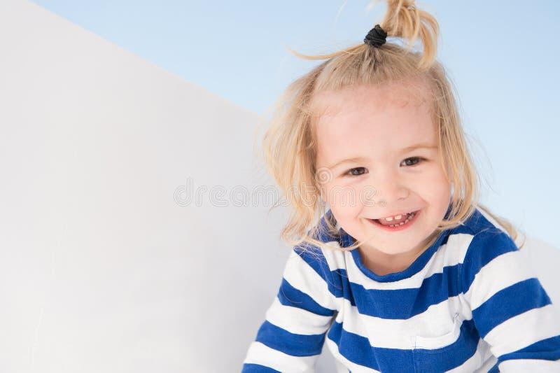 在海军衣裳的小男孩微笑 愉快的孩子享受晴天 微笑与金发马尾辫的孩子 孩子塑造并且称呼 Summe 免版税库存照片