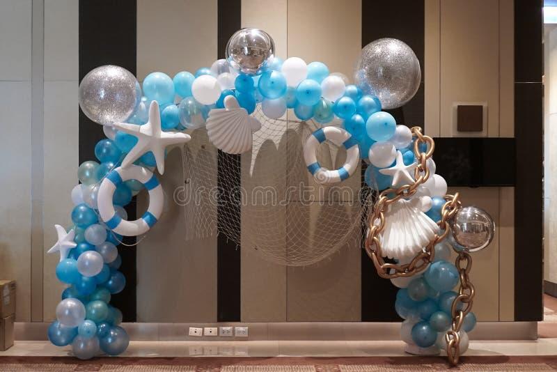 在海和夏天概念的气球 室内装饰的蓝色和白色气球与海星、救生圈和贝壳 库存照片