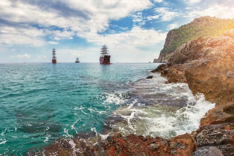 在海和多岩石的海滩的惊人的看法在与云彩和船的夏日在天际 海岸线海景与岩石和山的 图库摄影