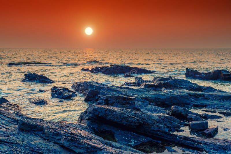在海和岩石岸的明亮的橙色太阳 免版税库存图片