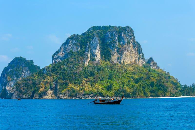 在海和岩石, Krabi,泰国的长尾巴小船 库存图片