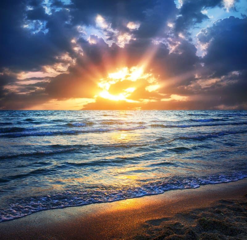 在海和波浪的日落在海滩 美好的日落 免版税库存照片