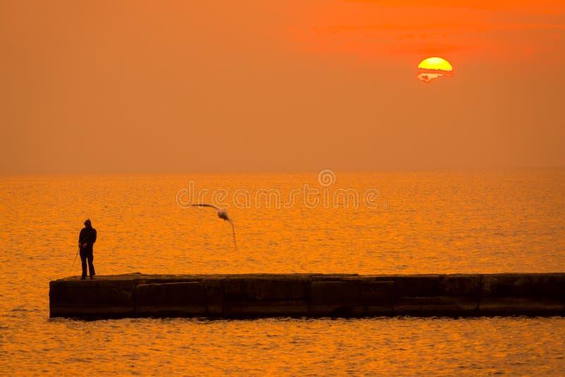 在海和渔夫的日落码头的 免版税库存图片