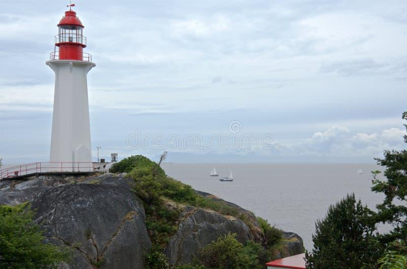 在海和灯塔的风船在海岸岩石 库存照片