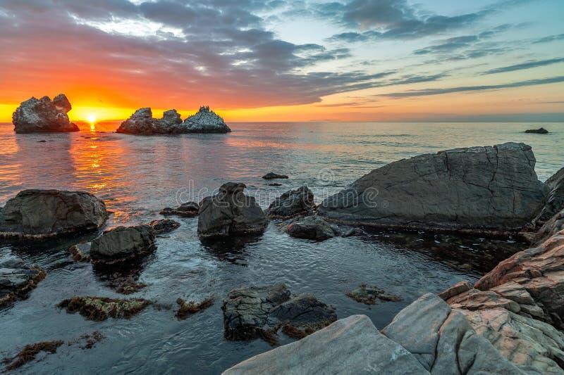 在海和石岸的日落 库存照片