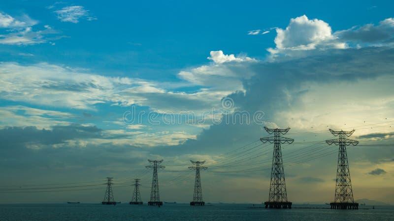 在海和蓝天的输电线 免版税库存照片