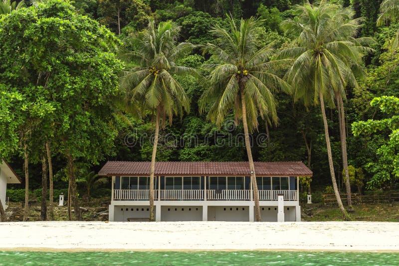 在海岛上的一栋小别墅和一个小森林的背景 免版税图库摄影