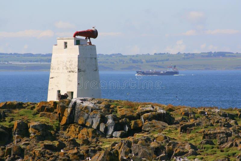 在海岛上的警告号角有通过的船 库存照片