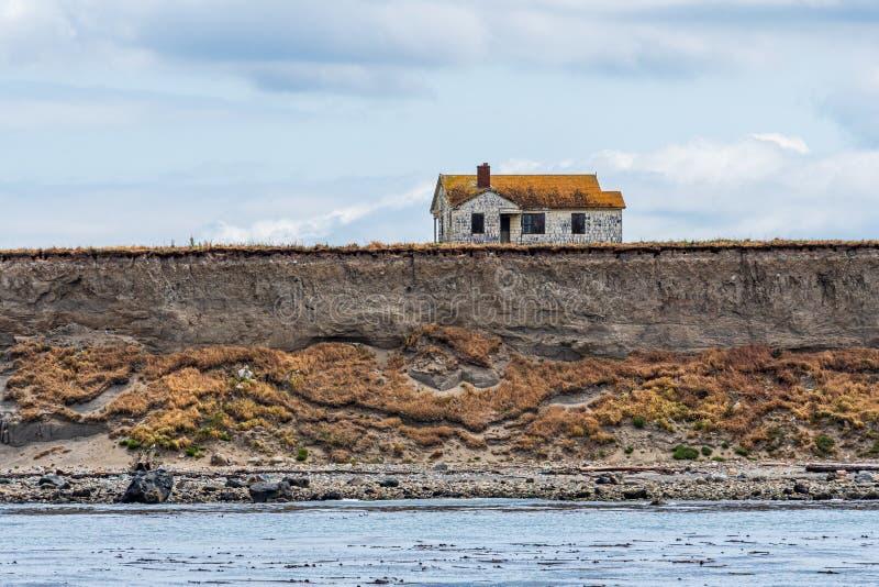 在海岛虚张声势边缘的被放弃的房子腐蚀和落入Salish海,圣胡安海岛,风平浪静和多云 免版税库存图片