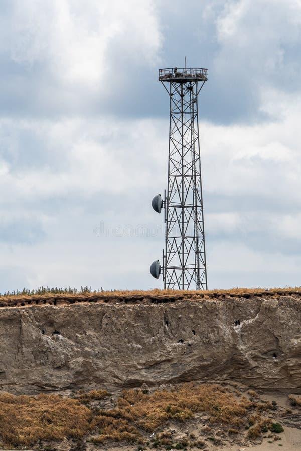 在海岛虚张声势边缘的通讯台腐蚀和落入Salish海,圣胡安海岛,阴天,美国 库存图片
