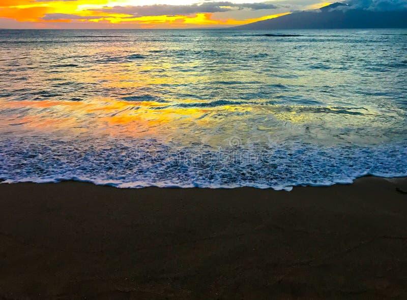 在海岛黑色沙子海滩的日落 免版税图库摄影