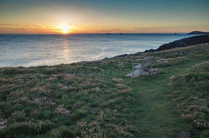 在海岸偏僻的长凳和海桃红色的日落开花康沃尔郡E 库存照片