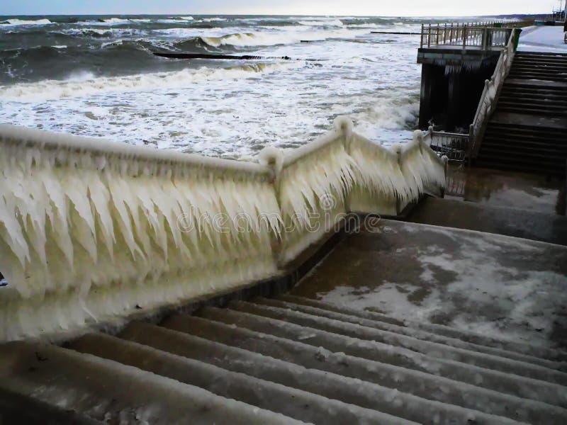 在海岸增加的湿气的冻扶手栏杆 库存图片