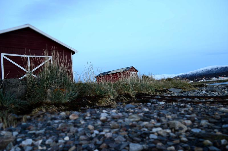 在海岸旁边的老红色船库 免版税库存照片